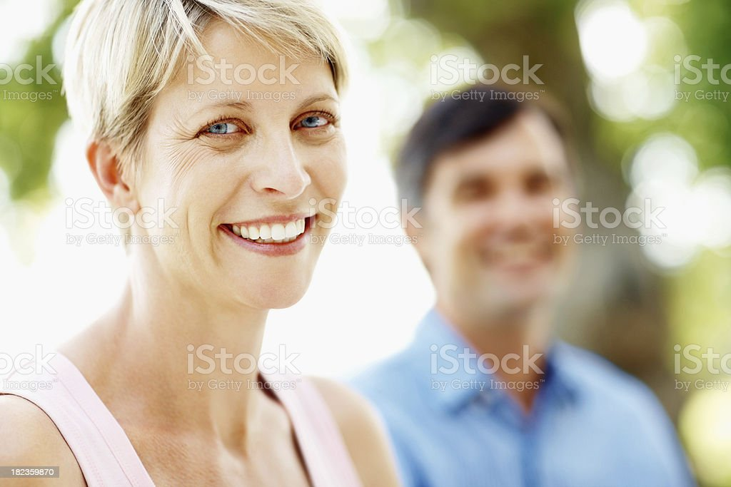 Beautiful woman smiling with husmand at the back royalty-free stock photo