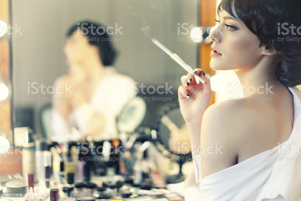 Beautiful woman smokes cigar with a cigarette holder stock photo