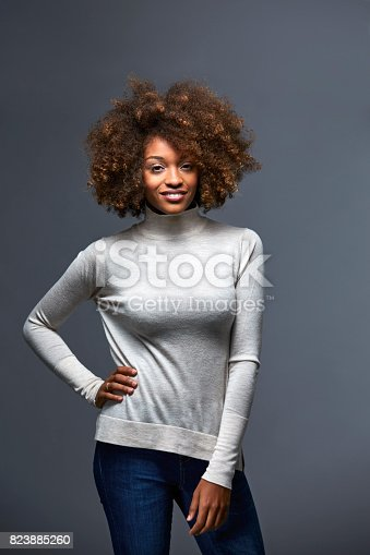 Beautiful young woman standing against gray background. Portrait of confident female with hand on hip. She is with curly hair.