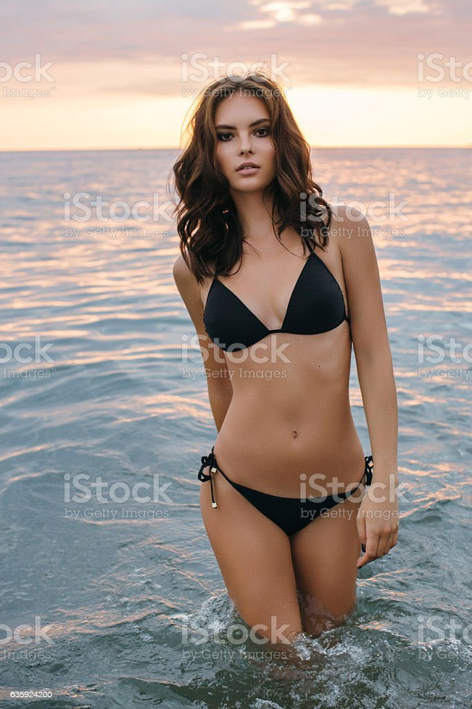 Beautiful woman standing at the sea stock photo