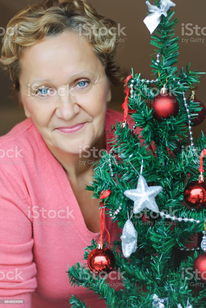 beautiful woman standing beside a Christmas tree stock photo