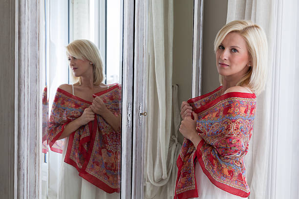 beautiful woman standing in front of mirror - carolinemaryan stock pictures, royalty-free photos & images
