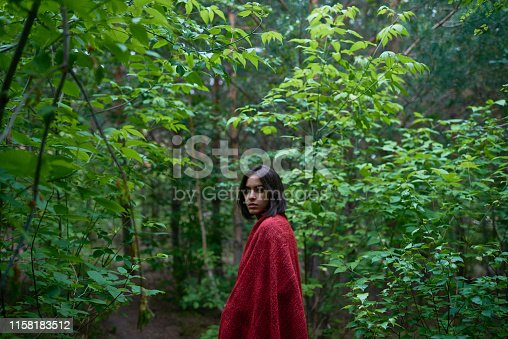 Side view of modern young brunette in red cloth looking at camera while standing in tranquil empty woods