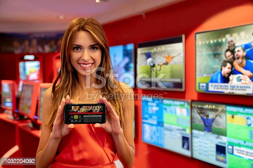 1032204252 istock photo Beautiful woman standing next to live sports betting at the casino while holding a smartphone showing her bets 1032204092