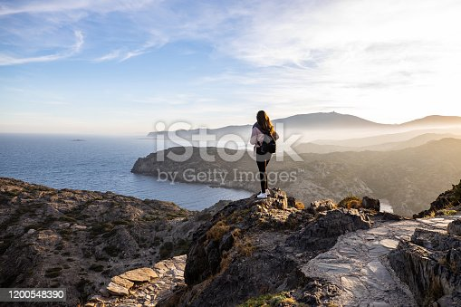istock Beautiful woman standing on a cliff during sunset with the mediterranean sea in the background at Cap de Creus, in Spain with copy space 1200548390