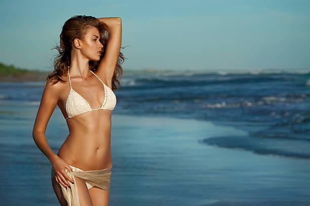 Beautiful woman standing on the beach foto