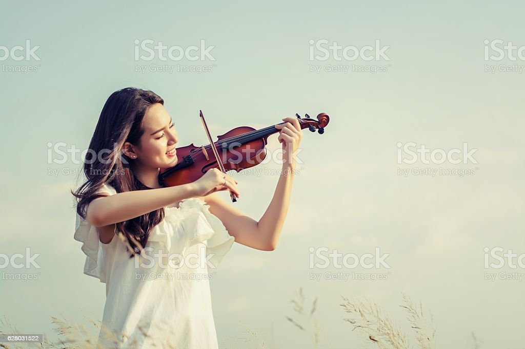 Beautiful Woman standing Playing the violin in the meadow stock photo