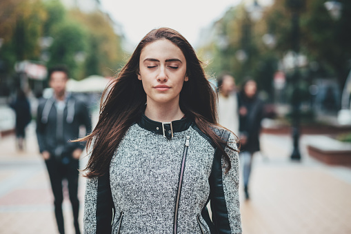 Beautiful woman standing with eyes closed on the street