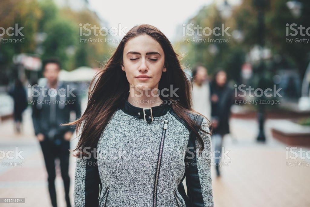Hermosa mujer de pie con los ojos cerrados en la calle - foto de stock
