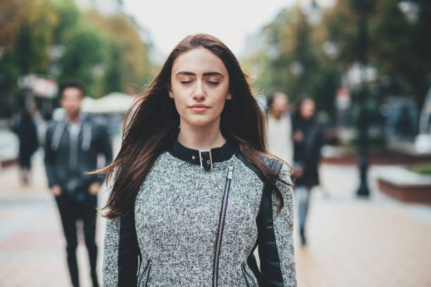 Beautiful woman standing with eyes closed on the street stock photo