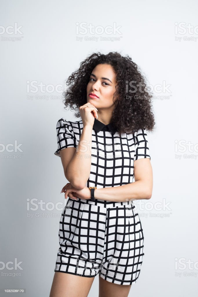 Beautiful woman standing with hand on chin Portrait of beautiful young woman standing with her hand on chin and staring at camera against gray background 20-24 Years Stock Photo
