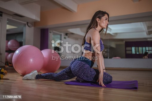 One woman, stretching on the floor in gym.