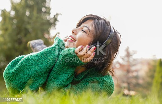 969233490 istock photo beautiful woman stretching on the grass listens to music 1199777527