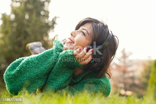 969233490 istock photo beautiful woman stretching on the grass listens to music 1199777529