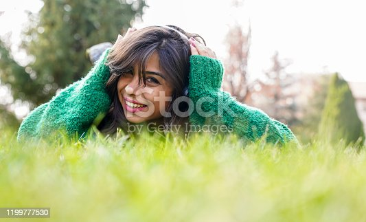 969233490 istock photo beautiful woman stretching on the grass listens to music 1199777530