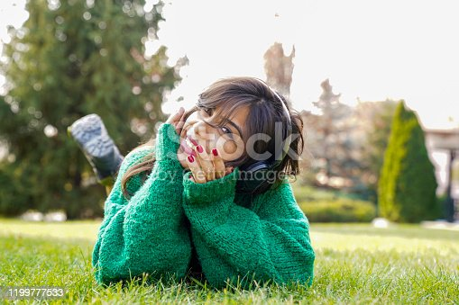 969233490 istock photo beautiful woman stretching on the grass listens to music 1199777533