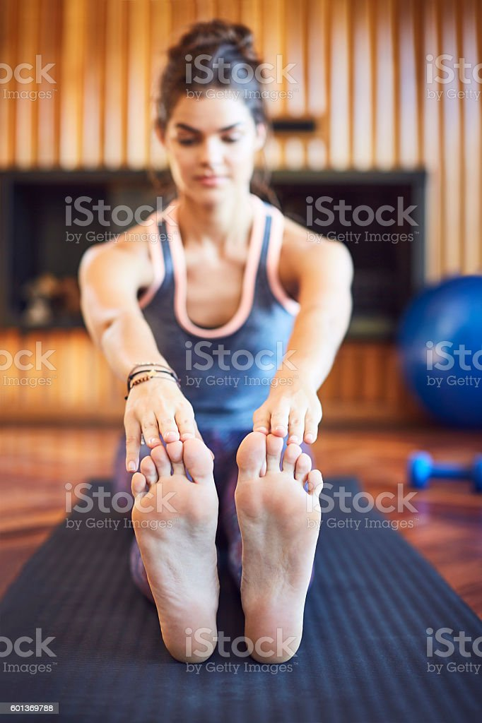 Beautiful woman stretching toe touch exercise on mat at home stock photo