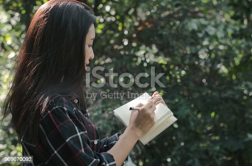 Beautiful woman student take notes using pen writing on paper on the study of nature in the park. education in natural concept.