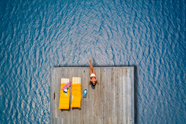 Beautiful woman sunbathing alone on a wooden pier in sea aerial photo stock photo