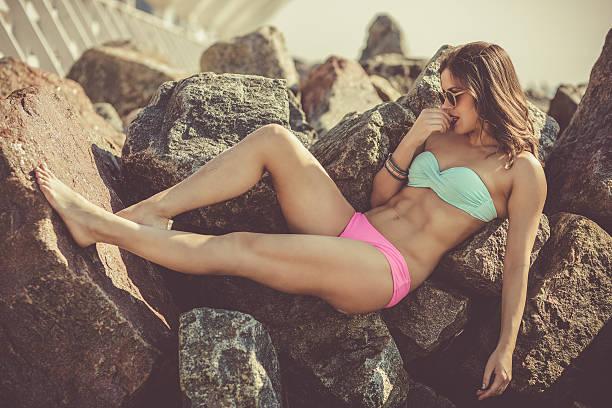 Beautiful woman sunbathing at the rocky beach stock photo