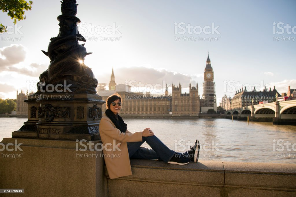 Beautiful woman takes a photo in front of parliament in London, England stock photo