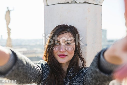 beautiful young woman takes a selfie on the roof of Milan Cathedral.