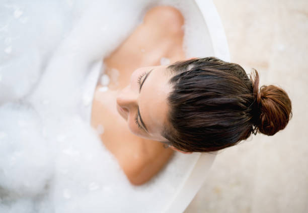 Beautiful woman taking a bath Beautiful woman taking a bath and relaxing at home - lifestyle concepts bathtub stock pictures, royalty-free photos & images