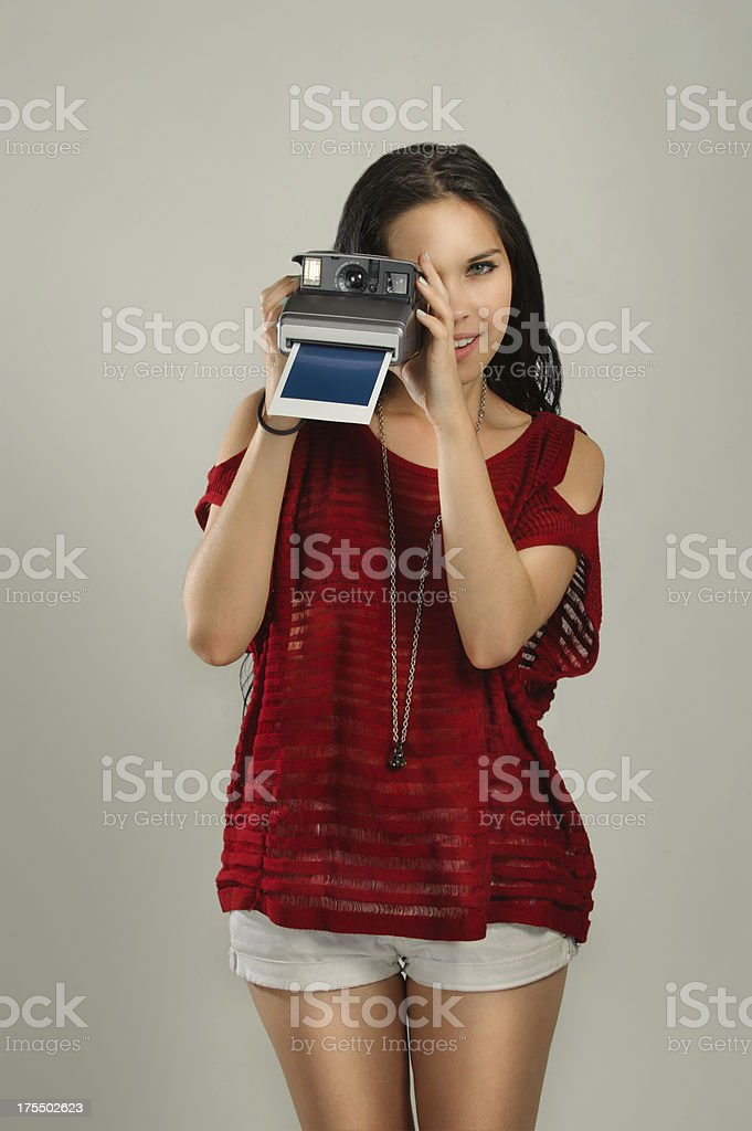 Beautiful Woman taking a picture with an instant camera stock photo