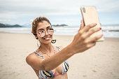 istock Beautiful Woman taking a selfie at beach 1068340882