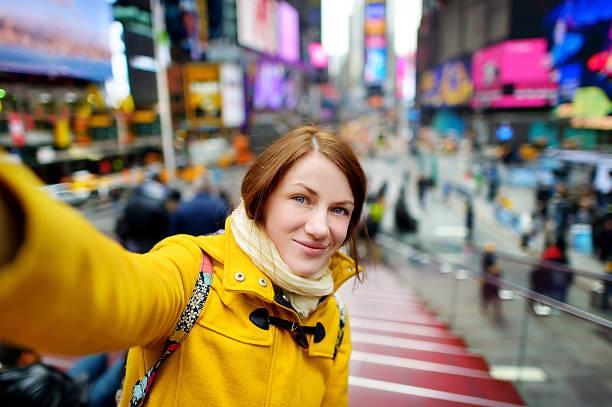 schöne frau, die ein selfie auf den times square - sightseeing in new york stock-fotos und bilder