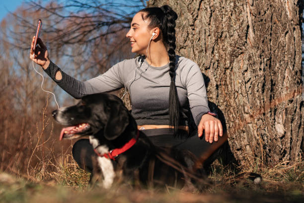 Beautiful woman taking a selfie with her dog after workout stock photo