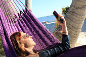 Young beautiful long hair woman taking selfie by using mobile phone and relaxing in hammock on the sandy beach in Key West, Florida