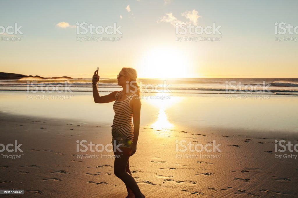 Beautiful woman taking selfie at beach royalty-free stock photo