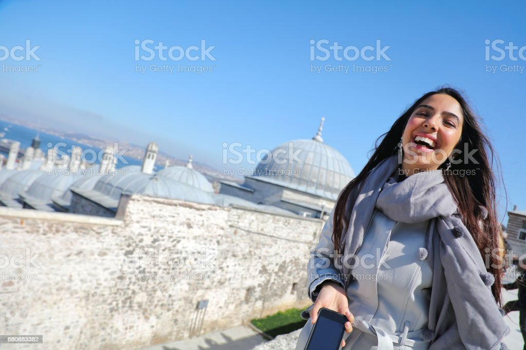 Beautiful woman taking selfie at the Suleymaniye Mosque enjoying the amazing view of Istanbul, Turkey royalty-free stock photo