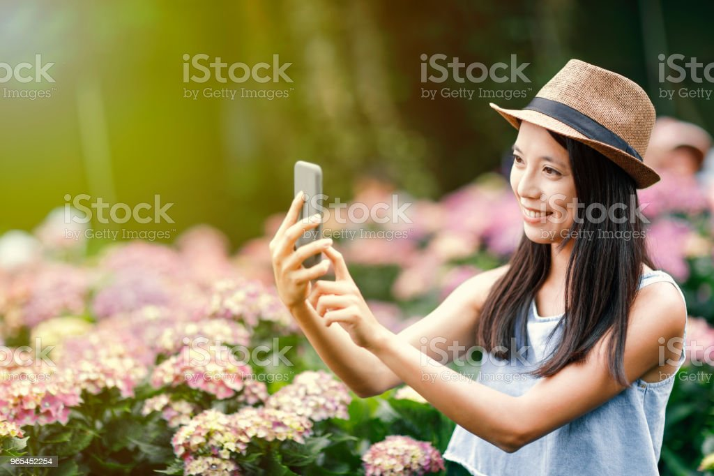 beautiful woman taking selfie in garden royalty-free stock photo