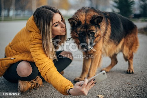 636418612 istock photo Beautiful woman taking selfie with dog in the park 1199430808