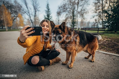 636418612 istock photo Beautiful woman taking selfie with dog in the park 1199646814