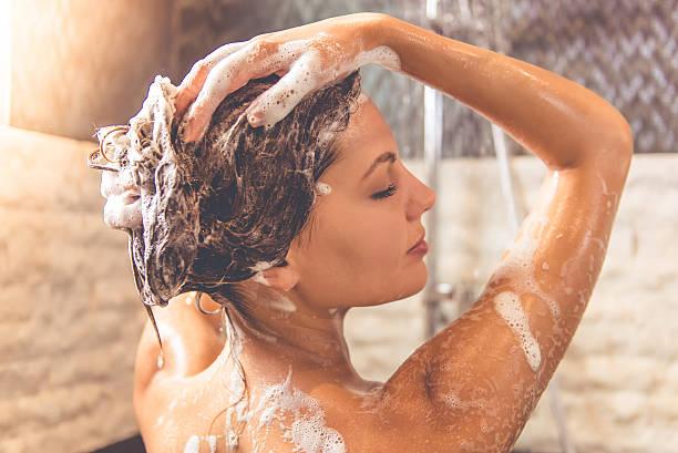 Beautiful woman taking shower stock photo