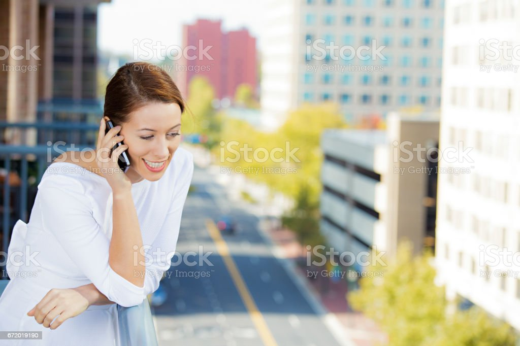beautiful woman talking on cell, mobile phone relaxed on balcony of her apartment stock photo