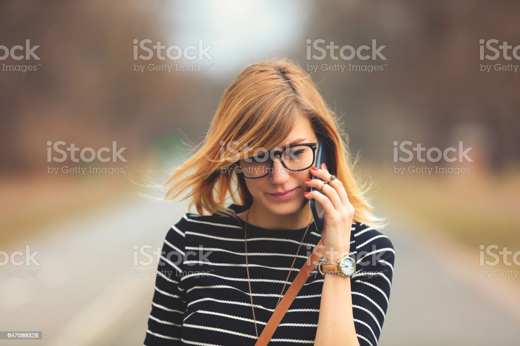 Beautiful woman talking on her cellphone outdoors. stock photo