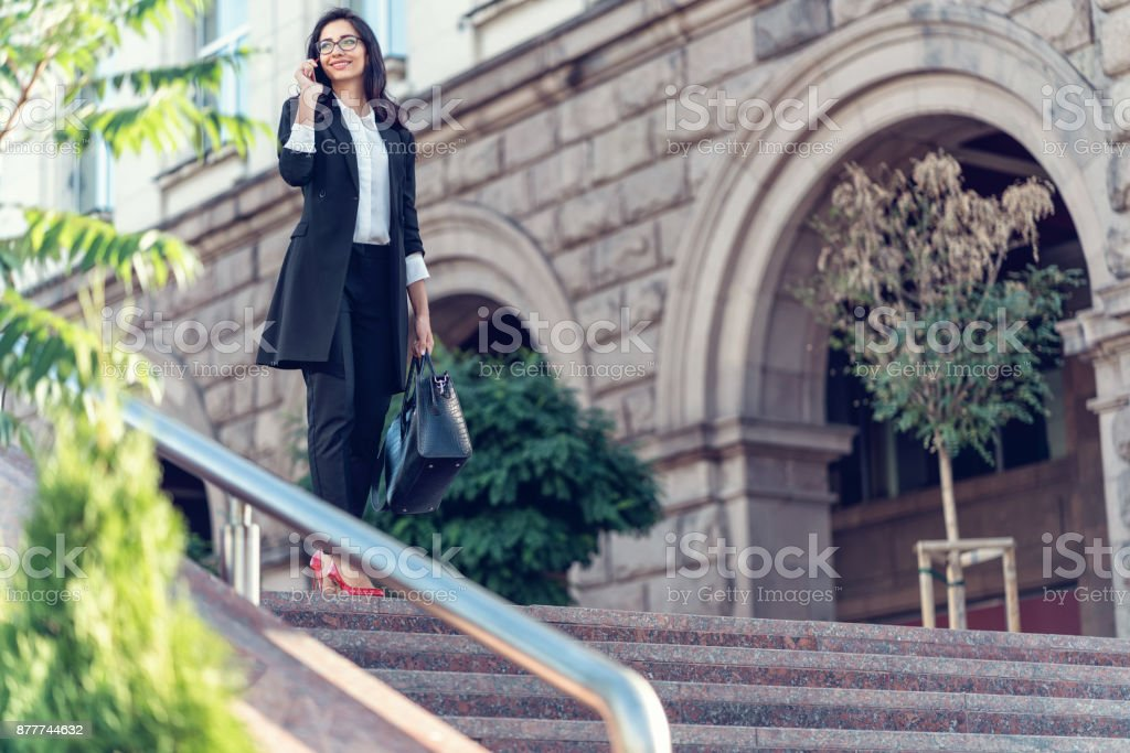Beautiful woman talking on the phone while going down the staircase stock photo