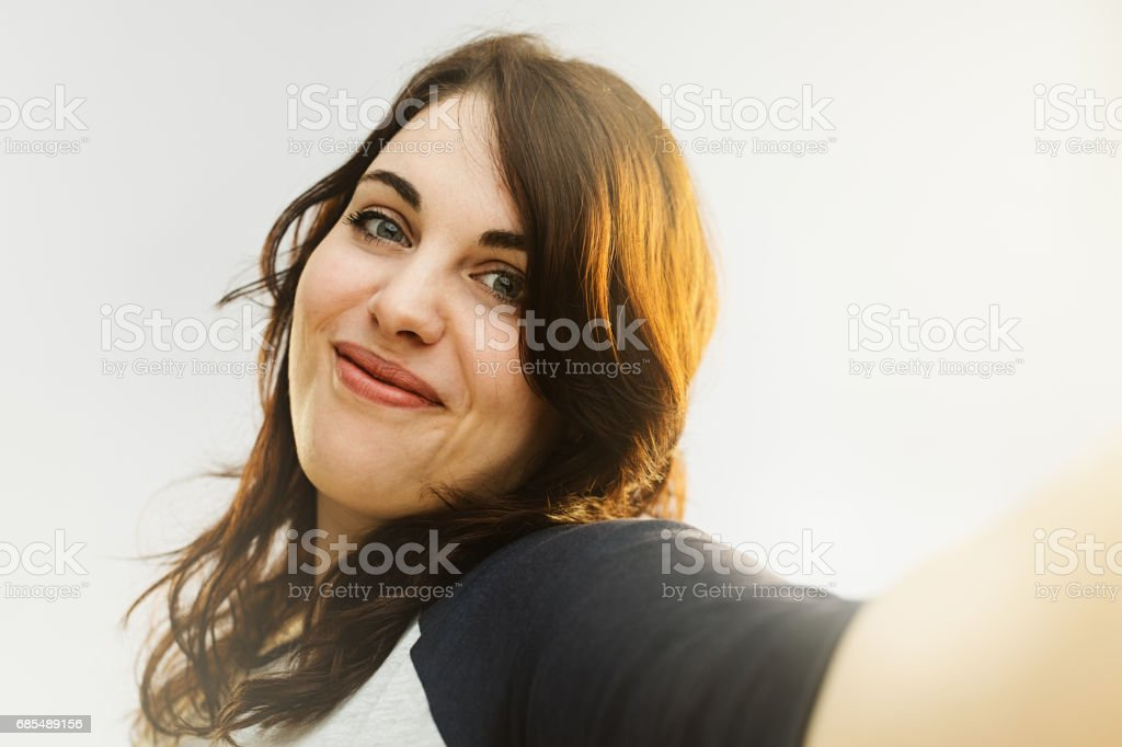 Beautiful woman talking selfie against gray background. stock photo