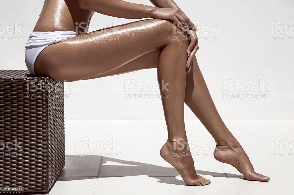 Beautiful woman tan legs. Against white wall. stock photo