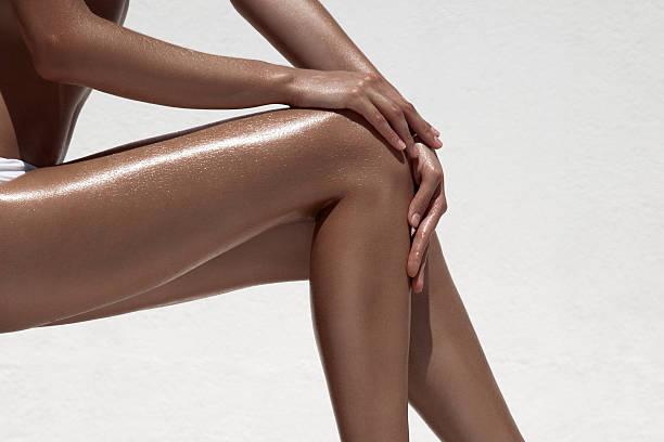 Mulher bonita tan pernas. Contra a parede branca. - foto de acervo