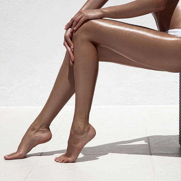 Beautiful woman tan legs. Against white wall. stock photo