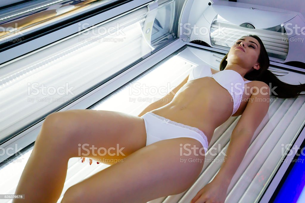 Beautiful woman tanning in solarium stock photo
