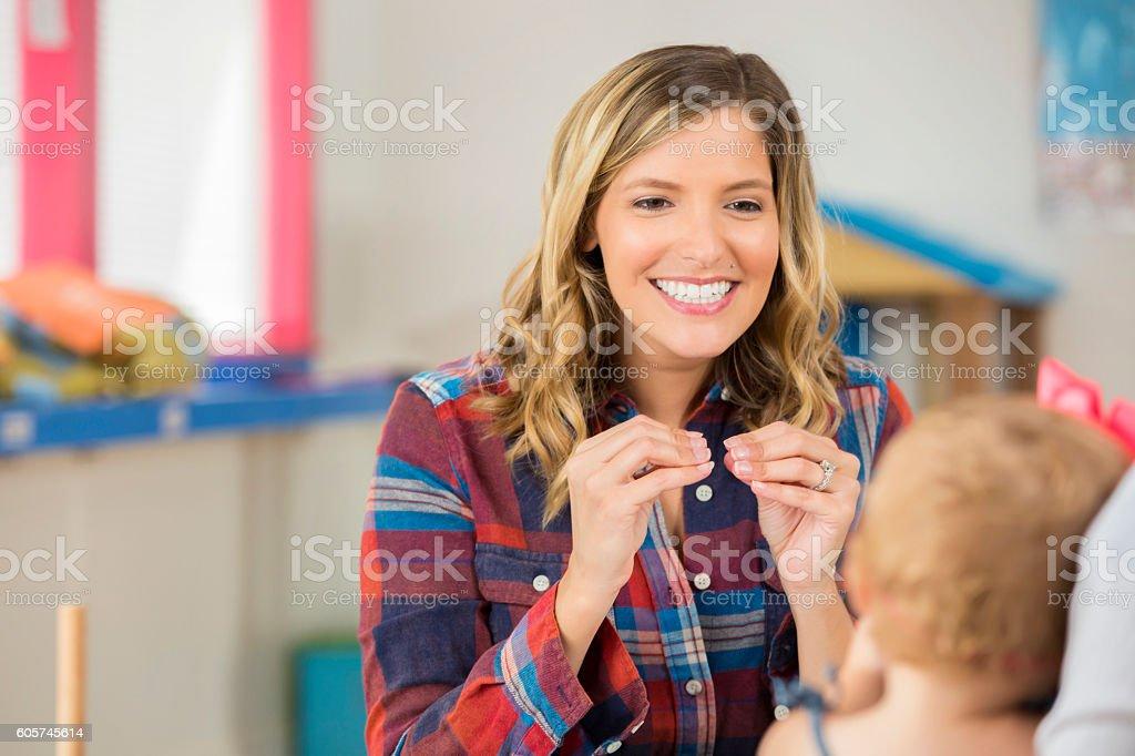 Beautiful woman teaching preschooler sign language stock photo