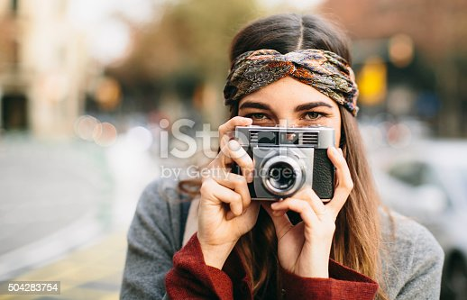 Beautiful woman teasing with a retro camera.