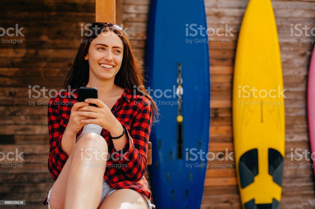 Beautiful woman texting at a beach bar zbiór zdjęć royalty-free