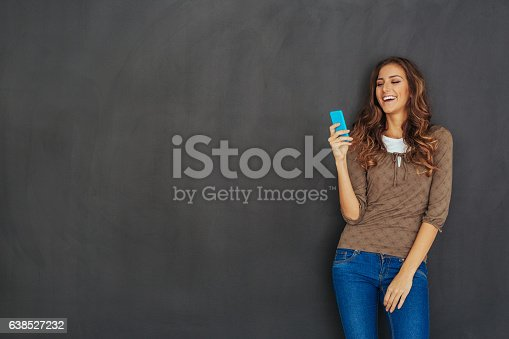 istock Beautiful woman texting in front of an empty blackboard 638527232